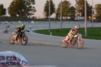 Doug Lawrence (# 1 Rotax) gets in front of rival Dave Pouliot (# 16 Kawasaki) on the charge to the line for the win on the last lap of their Feature class heat race at dusk at Georgian Downs. [Photo: Colin Fraser]
