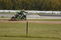 In the last E.M.R.A. race of 2019 at Castrol Raceway, soon-to-be-Champ Ryan Boddy, aboard a Kawasaki ZX-10R Ninja, runs off-road but stays on two wheels in turn four, ending his challenge for Feature race winner and outgoing Champ Ian Wall. [Photo: Colin Fraser]